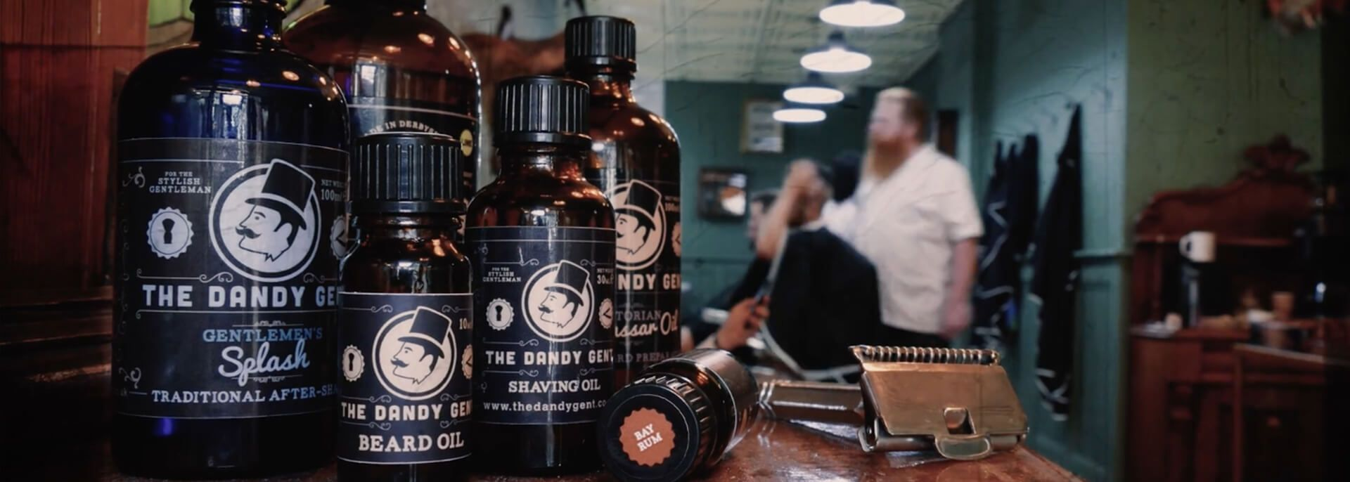 The Dandy Gent Beard Oil, Splash, Shave Oil displayed with Master Barber, Shane O''Shaughnessy in the background cutting hair in his Derby, UK-based Traditional Barber shop.